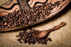 pile of fresh and bio aromatic coffee beans and spoon - stock photo