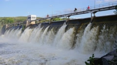 Three people cross the dam mills Stock Footage