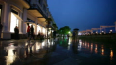 People go in rain on embankment in seaside southern city in summer evening - stock footage