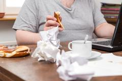 untidy desk and a overweight man with food in his hands - stock photo