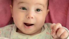 Close-up of baby girl's face. Funny babbling Stock Footage