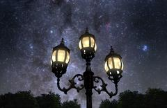Vintage looking lamp post against beautiful starry sky Stock Photos