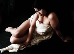 Seminude hispanic woman partialy covered with a white sheet - stock photo