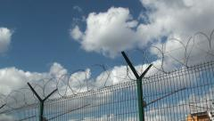 Secured area with a tower, a fence and barbed wire - stock footage