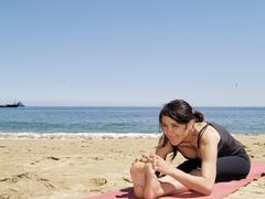 Bikram yoga sit-up pose at beach - stock photo