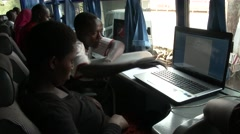 Inside a computer classroom in africa - Teacher helping student - stock footage
