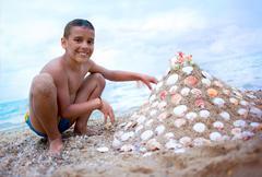 Boy on the beach play with sands Stock Photos