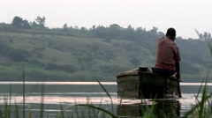 African fisherman in a boat crossing the river Stock Footage