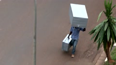 Man carrying heavy stuffs alone in the street Stock Footage