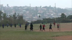 A group of African schoolboys and girls playing soccer near the city Stock Footage