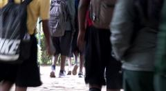 A group of school kids walking out of school Stock Footage