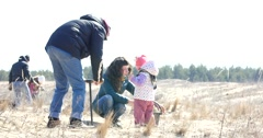Volunteer parents with little kid girl planting pine forest in a desert steppe Stock Footage