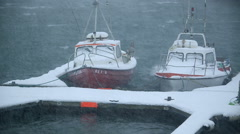 Small boats in Reykjavik harbor rocking in heavy winds and rough water, snowy Stock Footage