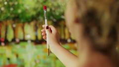 Young painter painting with brush and oil paint - stock footage