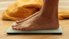Feet stepping onto a scale, close up shot Stock Footage