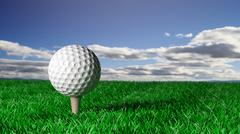 Golf ball on tee on grass with blue sky Piirros