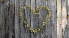 Golden chain in shape of heart, on wooden background - stock illustration