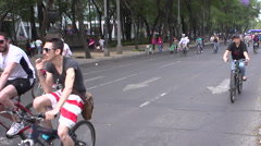 BPMX19-Mexico, woman on bike, dozens ride in the BG. Handheld, pan, medium shot. Stock Footage