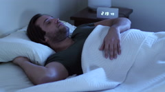 Young man having trouble sleeping, tossing and turning Stock Footage