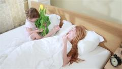 Cute baby brings flowers to her mother in bed in the morning. Stock Footage