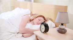 Young red-haired woman does not want to get up in the morning. - stock footage