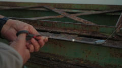 FISHERMAN CUTTING FISHING LINE WITH SCISSORS Stock Footage