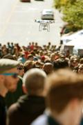 Flying Drone Hovers Over Crowd At Fair - stock photo