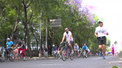 BPMX18-Mexico, two joggers & dozens of bikes on street. Low angle, wide. Stock Footage