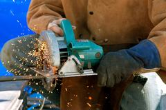 Sparks Fly As Man Cuts Rebar With Power Saw Stock Photos