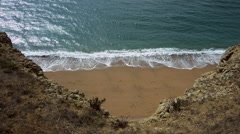 Looking down from high cliffs to sandy beach and sea - 4K Stock Footage
