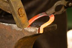 Hammering glowing steel - to strike while the iron is hot. Stock Photos