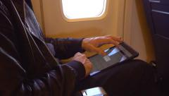 4k man using tablet pc ipad on airplane plane writing typing reading working Stock Footage