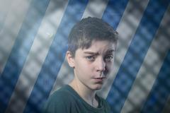 portrait of a doubting teenage boy with flare, striped background and shadow  - stock photo
