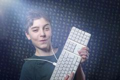 Smiling teenage boy with computer keyboard and letters salad as background Kuvituskuvat