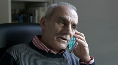 Angry old man is having a phone call with a mobile phone Stock Footage