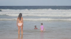 Young mother supervisors children in sea Stock Footage