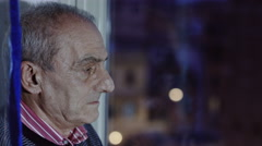 Old depressed man looking out the window with night city lights in background Stock Footage