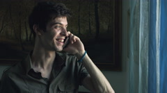 Happy young man is having conversation with the mobile phone at home Stock Footage