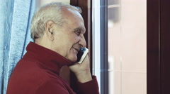 old man talking with someone with a modern smartphone - stock footage