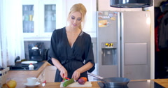 Stylish woman preparing dinner in the kitchen Stock Footage