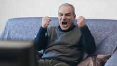 Change of focus on old man watching a football match: anger, emotions, exults Stock Footage