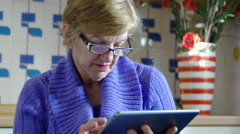 Elederly woman surfing on internet with her tablet computer: housewife, kitchen Stock Footage