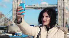Tourist woman is making a selfie with London Tower bridge in background Stock Footage