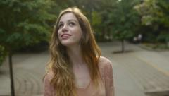 Young Woman Enjoys Walking Through Park, She Receives A Text And Smiles/Laughs Stock Footage