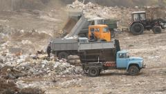 Garbage trucks on a dump Stock Footage
