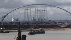 Sand mining in river landscape, Nijmegen industrial area in background - stock footage
