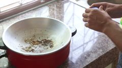 European man pours salt into frying pan Stock Footage