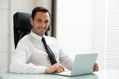 Half length portrait ofa male businessman, smiling at camera and working with Stock Photos