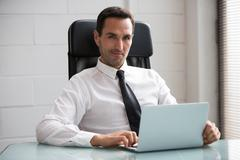 Half length portrait of a male businessman in the office, looking at camera a Stock Photos