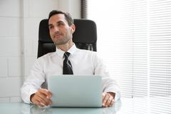 Half length portrait of a male businessman with earphones and laptop computer - stock photo